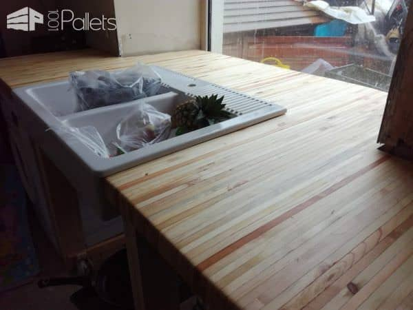 This Pallet Wood Kitchen features an end-grain pallet wood counter top done in a butcher block style.