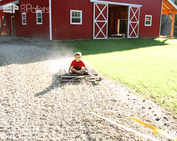Weird Wood ideas include putting your kids to work as anchors on a pallet drag chain to smooth your driveway.