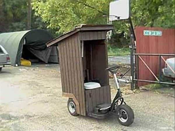 A Weird Wood creation of a tri-wheeled scooter with a small shed and toilet built over the seat area.