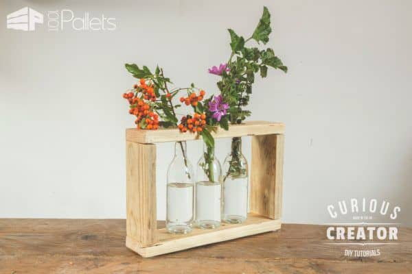 Make this Pallet Glass Vase Stand with the help of the DIY Video Tutorial. Then have fun emptying three clear bottles of your favorite beverage to complete it.