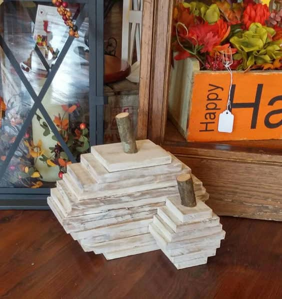 These pumpkins will never go bad. This Pallet Fall Centerpiece consists of two small pumpkins made by stacking graduated pieces of pallet wood to create a pumpkin shape, and a tree branch is used for the stem.