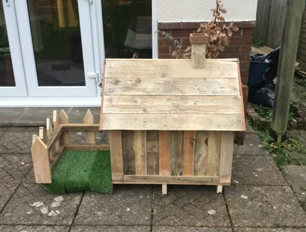 This Pallet Doghouse features an elevated sub-floor, a small front porch and a picket fence.