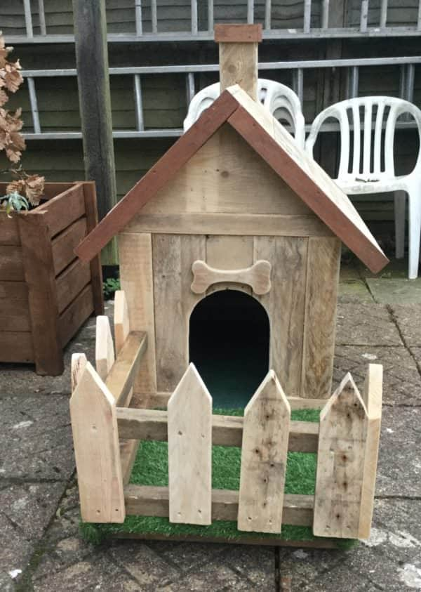 We added a little chimney, a picket fence and a front porch to this Pallet Doghouse.