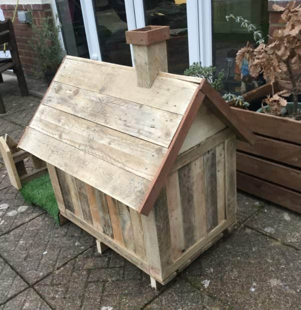 Rear view of this Pallet Doghouse shows the cute little chimney and painted trim.