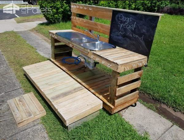 This Pallet Kid's Kitchen features a chalkboard, plenty of hooks for hanging things, a deck and steps.