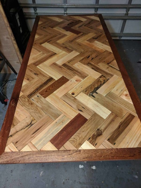 This Pallet Dining Table features a herringbone pattern and african hardwood border.