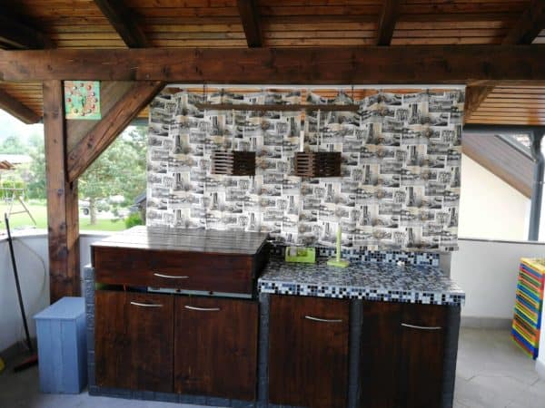 This outdoor Pallet Kitchen project features pallet wood for the cabinet doors, grill cover, lights and clock.