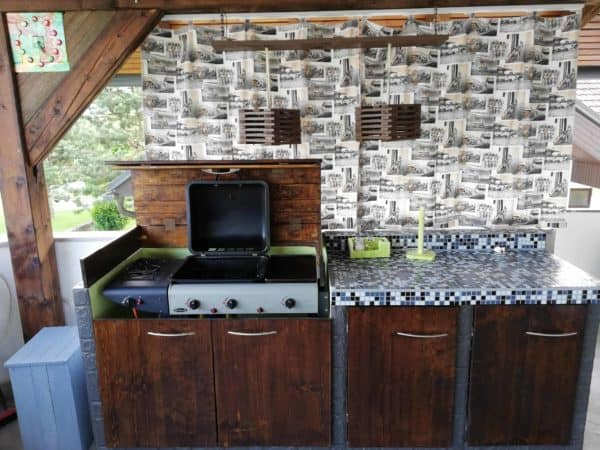The barbecue cover in the Pallet Kitchen is made of pallet wood and lifts/folds out of the way behind the grill lid.
