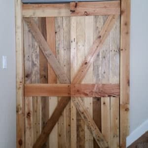 These Pallet Closet Doors are rustic, stylish, and make a dull hallway look extraordinary. Add a custom punched-metal piece on the top and you've got a one-of-a-kind creation that'll set your house apart!